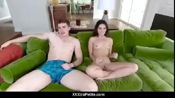 Irmãos transando no sofá verde da sala enquanto assistem televisão